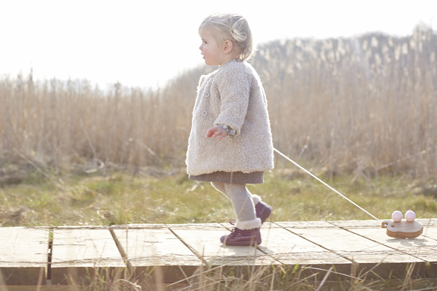 julia-bostock-kids-photographer-london-blond girl on a bridge toy, nature, eco toys, kids