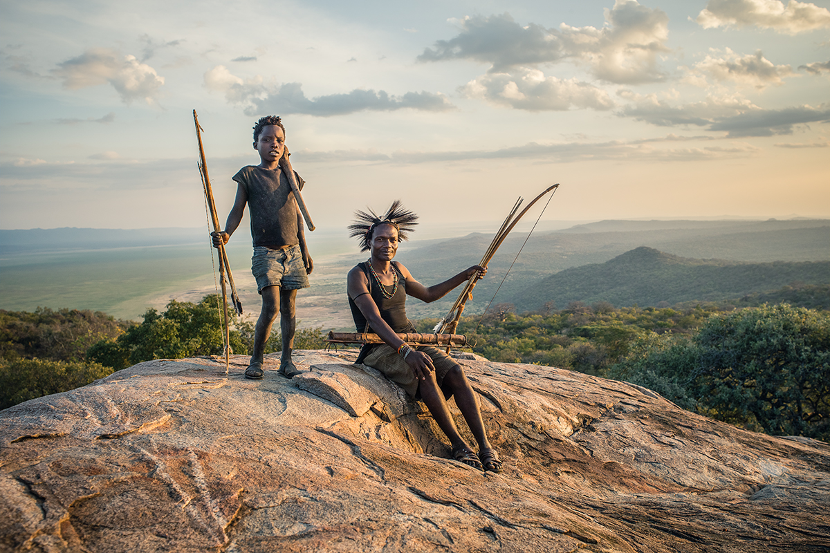 Hamesi Hasani a Hadza hunter wearing a zebra mane hat and his nephew ~10 year old Mkapa Kaunda standing on a rocky outcropping near their camp overlooking the Hadza Landscape of the Central Rift Valley, Tanzania.