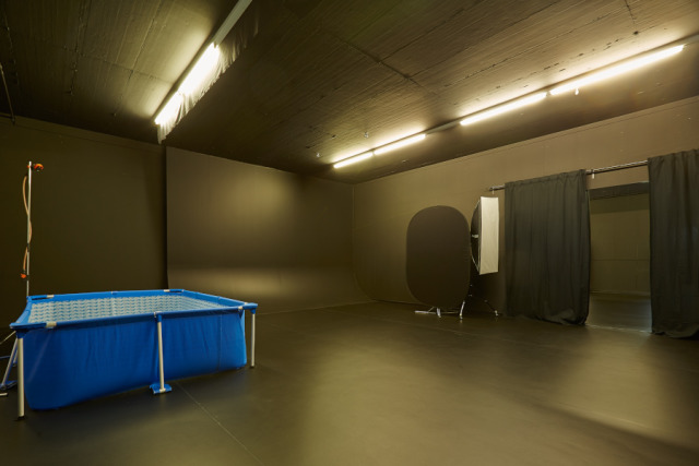 Low-key black room with cyclorama wall & water basin gallery